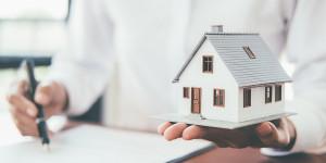 Frau hält Miniaturhaus in der Hand
