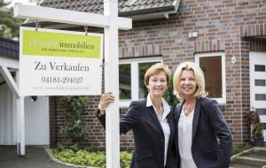 Immobilienmaklerin vor Haus