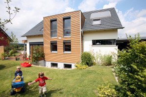 Einfamilienhaus mit spielenden Kindern im Garten