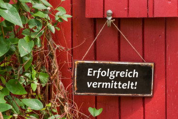 Schild an roter Hauswand