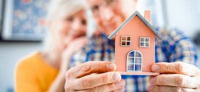 Älteres Ehepaar hält Miniaturhaus