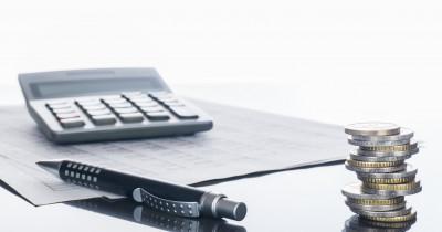 Taschenrechner mit Stift und Geld
