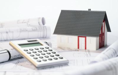 Baupläne mit Haus und Taschenrechner