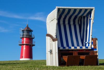 Strandkorb mit Leuchtturm im Hintergrund