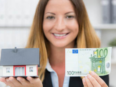 Frau hält Geldschein und Haus in den Händen