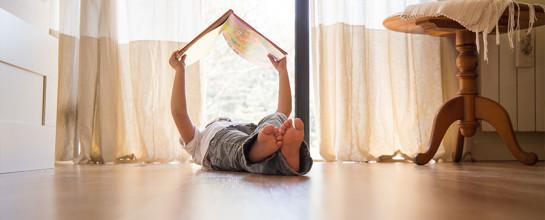 lesendes Kind mit Buch im Wohnzimmer