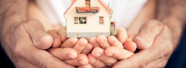 Familie mit Hausmodell in den Händen