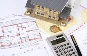 Hausmodell mit Grundriss und Taschenrechner