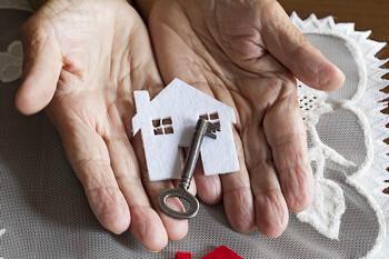Seniorin hält einen Schlüssel in den Händen