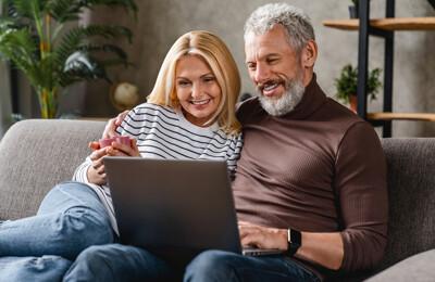 Glückliches Paar auf Sofa mit Laptop in den Händen