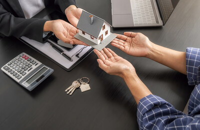 Übergabe des Hausmodells durch den Makler an den neuen Eigentümer