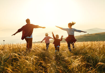 Familie läuft über Feld Richtung Sonnenuntergang