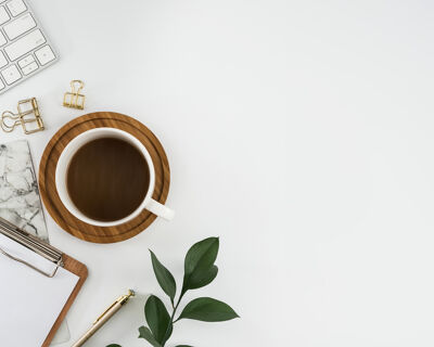 Tastatur, Kaffee und Klemmbrett auf weißem Tisch