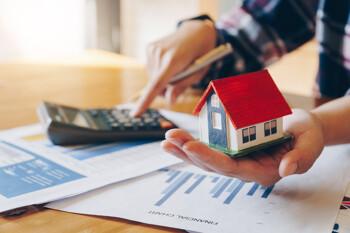 Makler berechnet etwas auf einem Taschenrechner, in seiner Hand hält er ein Hausmodell