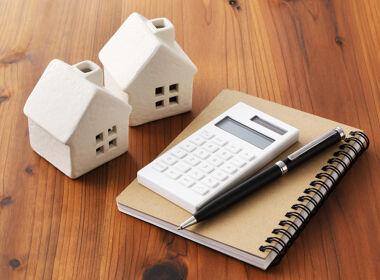 Häuser mit Taschenrechner und Notizblock