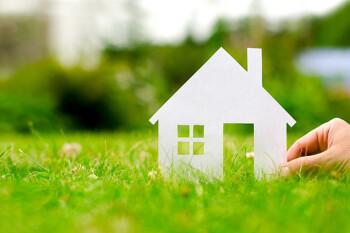 Hand hält Haus im Gras