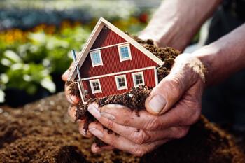 Hände halten Haus auf Erde auf einem Grundstück in Dornhan