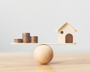 Hausmodell und Münzen auf der Waage
