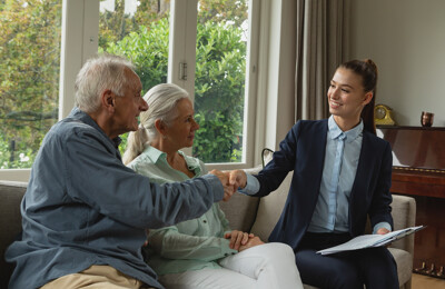 Makler berät älteres Ehepaar