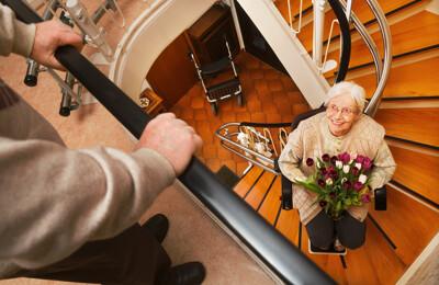 Ältere Frau im Treppenlift