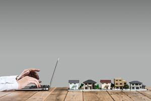 Makler mit einem Laptop und Hausmodellen auf dem Tisch