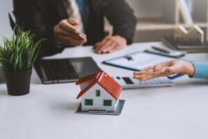 Makler mit Kunden bei der Beratung zur Immobilienfinanzierung
