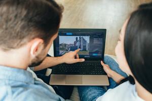 Ein Paar mit einem Laptop sucht eine Immobilie zum Kauf
