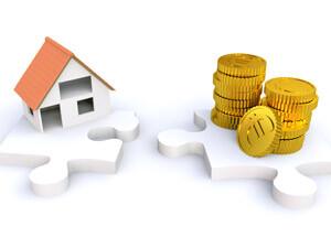 Haus und Münzen auf Puzzleteilen