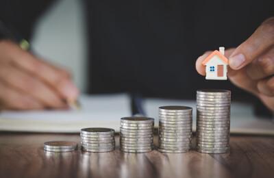 Der Makler platziert das Hausmodell auf der obersten Münzreihe