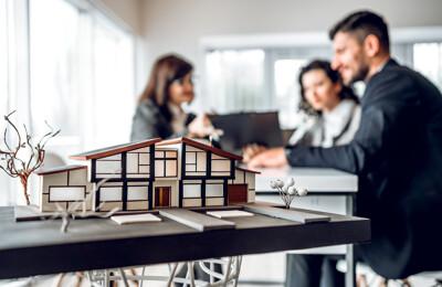 Makler berät ein Paar beim Kauf eines Hauses