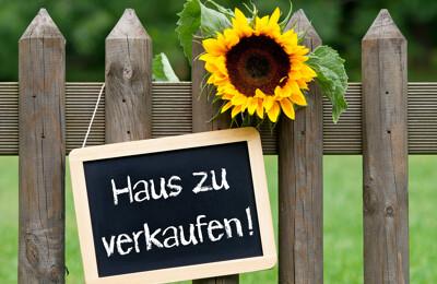 Hausverkaufsschild am Zaun mit Sonnenblume
