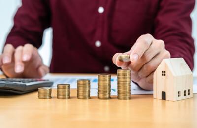 Makler mit Taschenrechner, Münzen und Modellhaus