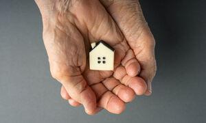 Seniorenhand hält Haus