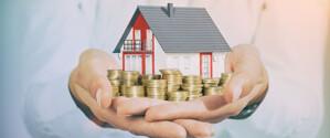 Haus und Münzen in Hand