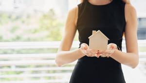 Frau mit Holzhausmodell in Händen