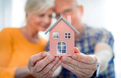 Seniorenpaar mit Modellhaus in Händen