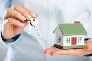Maklerin hält Schlüssel und Haus