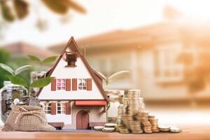 Miniaturhaus und Münzen