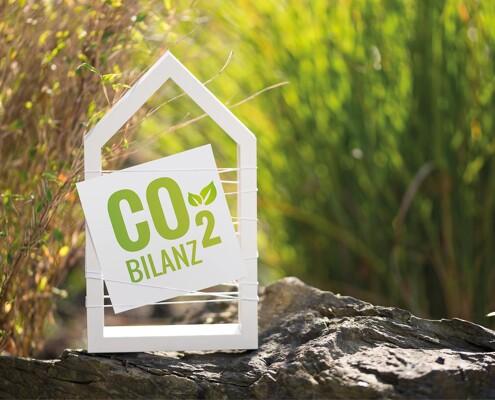 """Holzrahmen in Hausform mit Schild """"CO2 Bilanz"""""""