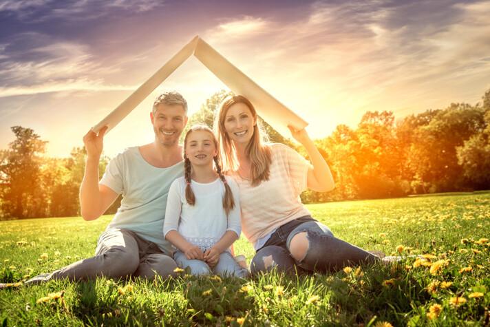 Familie auf Wiese mit Pappdach