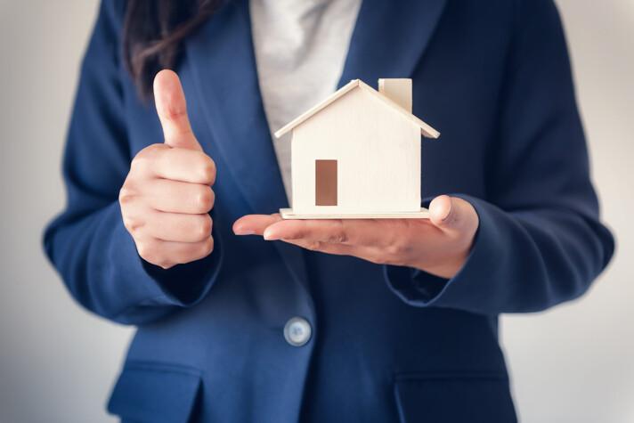 Frau mit Hausmodell in der Hand