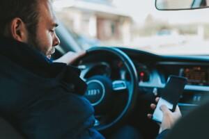 Autofahrer mit Handy in der Hand