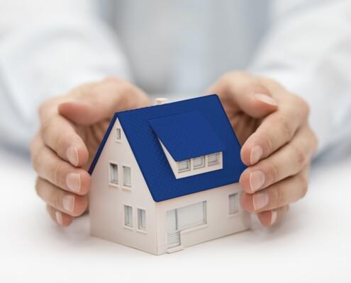 Hände halten ein Miniaturhaus