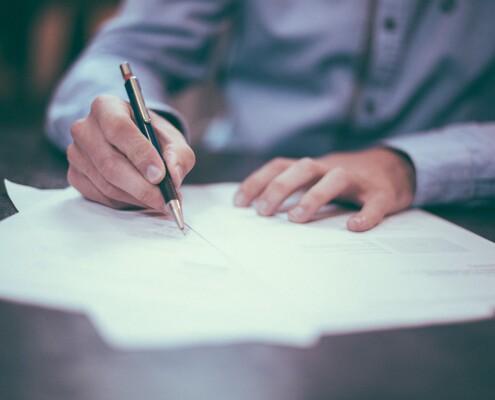 Mann unterschreibt Dokumente